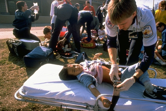 Young Asian girl, wounded in chest during shooting at Cleveland School by Patrick Purdy, being attended to by medical personnel.